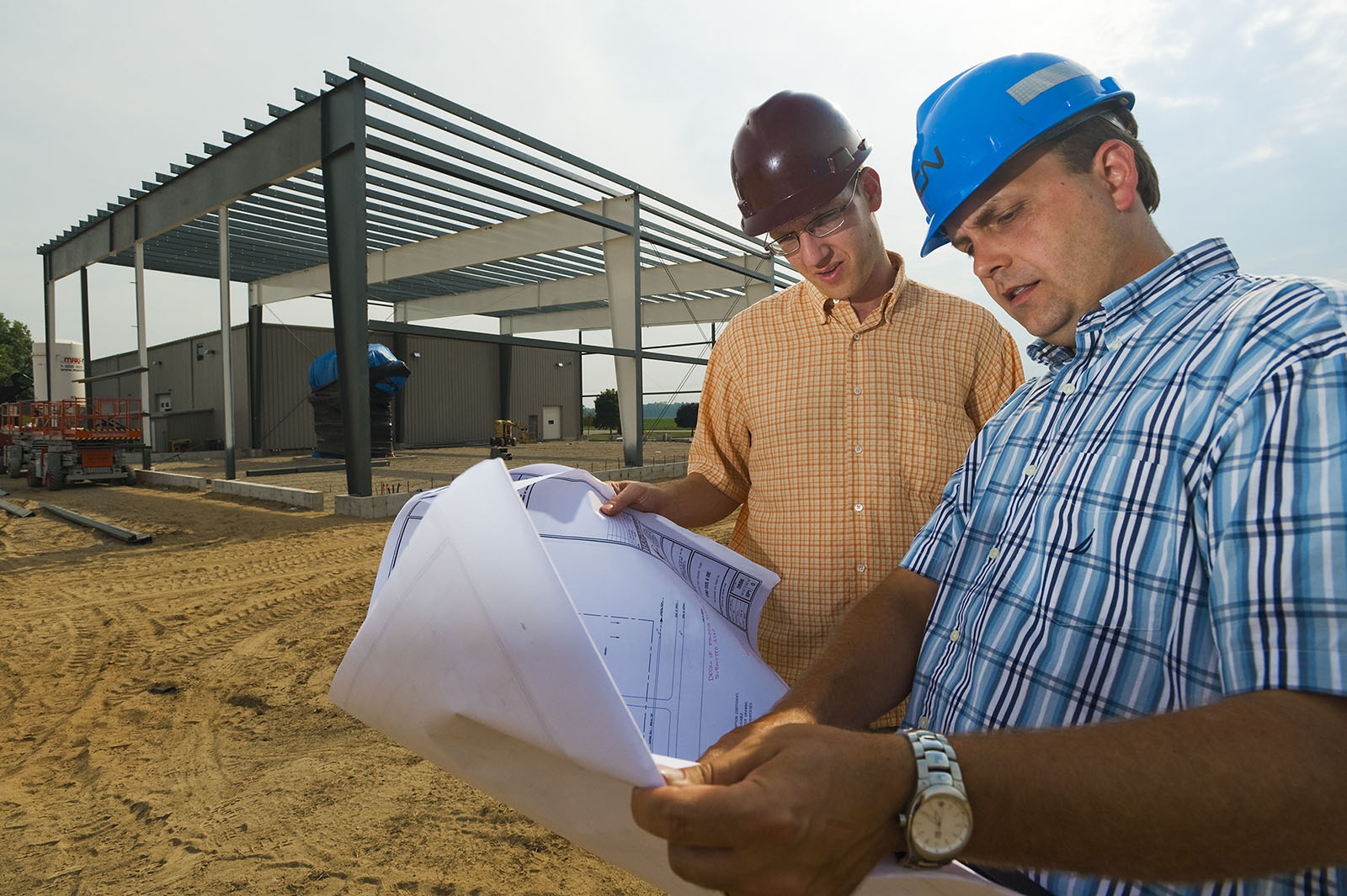 Two men look at blueprints on construction site