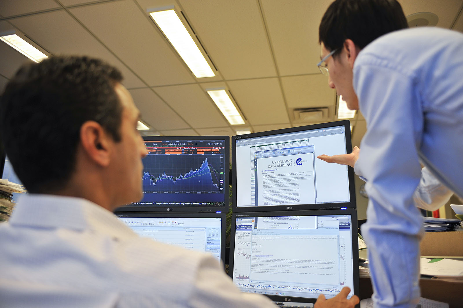 Two business analysts viewing data on computer screens