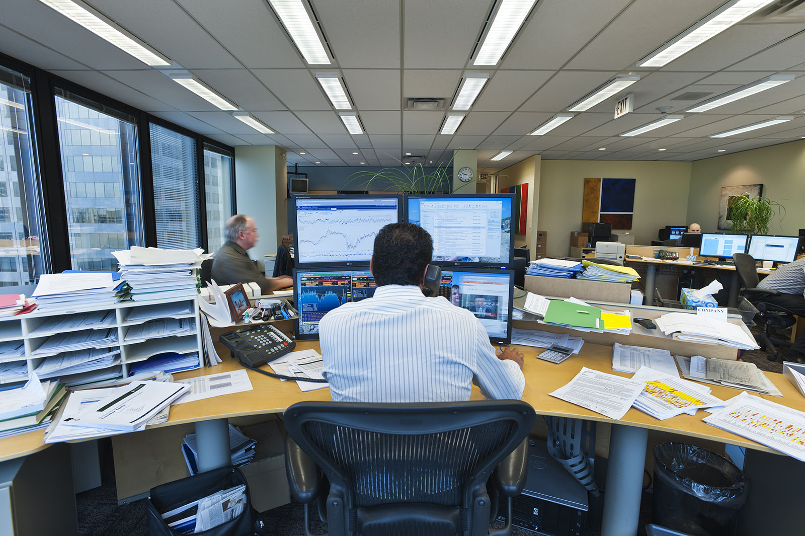 Rear view of a business analyst facing four computer screens