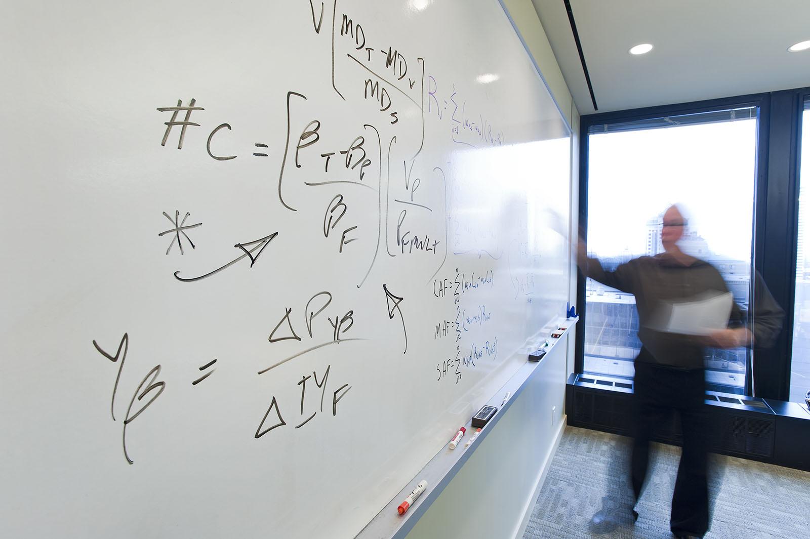 Philip Castleton Photography / Corporate portfolio / A man writing mathematical formulae on a large whiteboard.