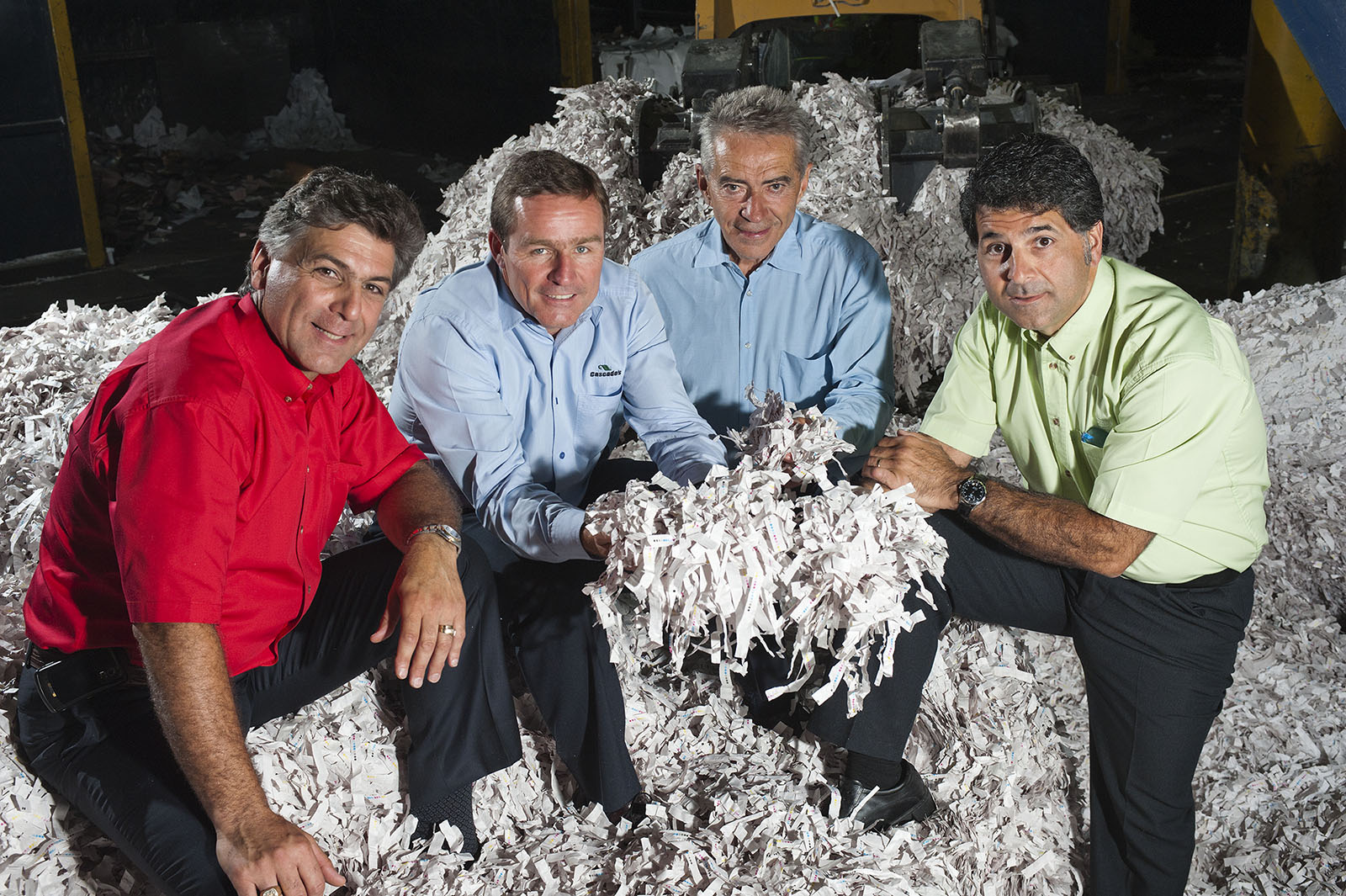 Four men examining shredded paper at Cascades recycling plant, Toronto, Ontario
