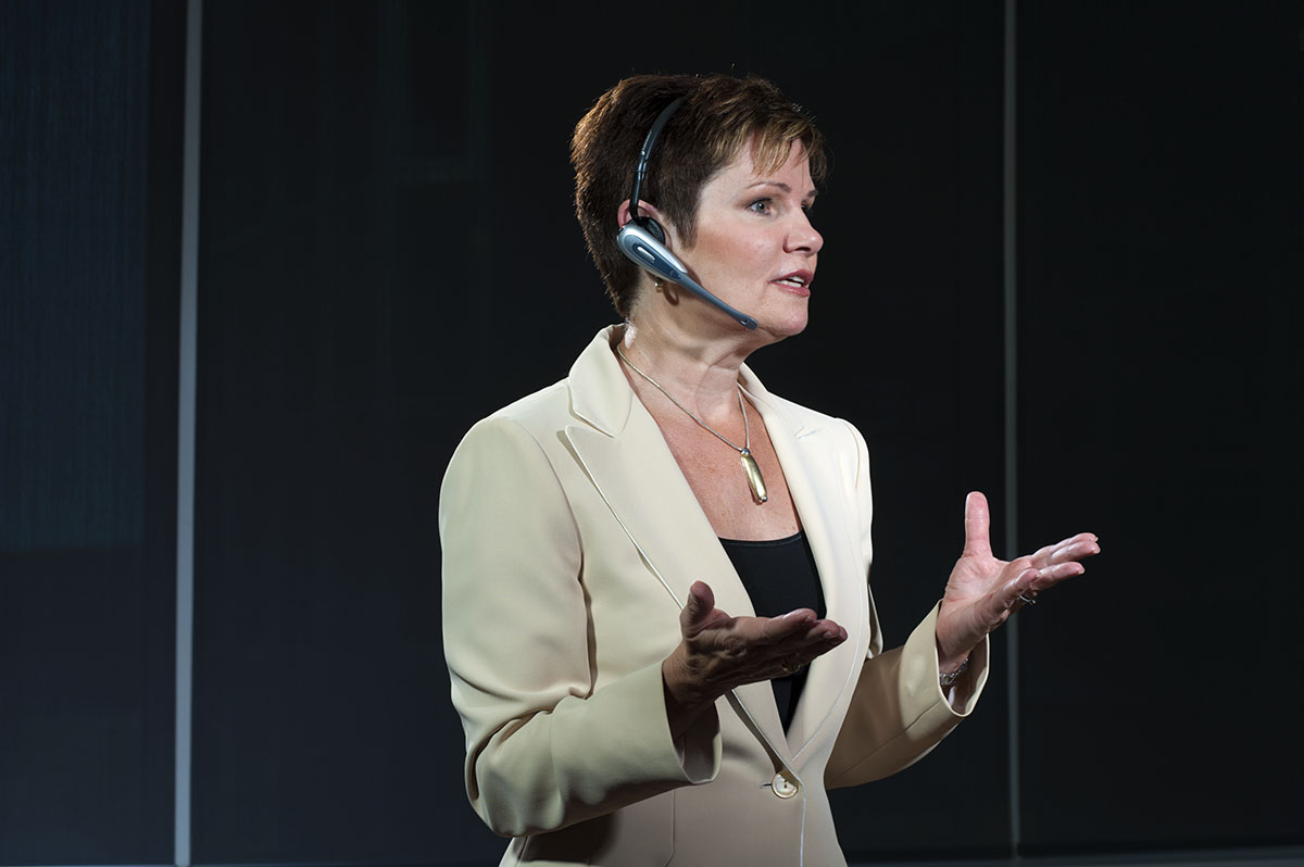 An executive speaking at a business event with hands gesturing.