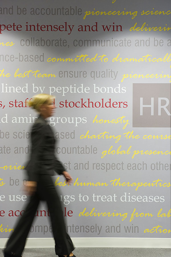 A female office worker walking in front of a wall inscribed with business phrases.