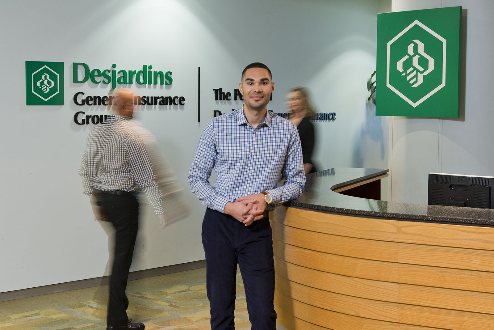Desjardins office reception area with one man leaning on desk