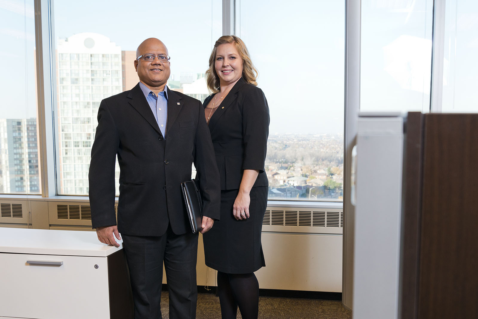 One businessman and one businesswoman in black suits