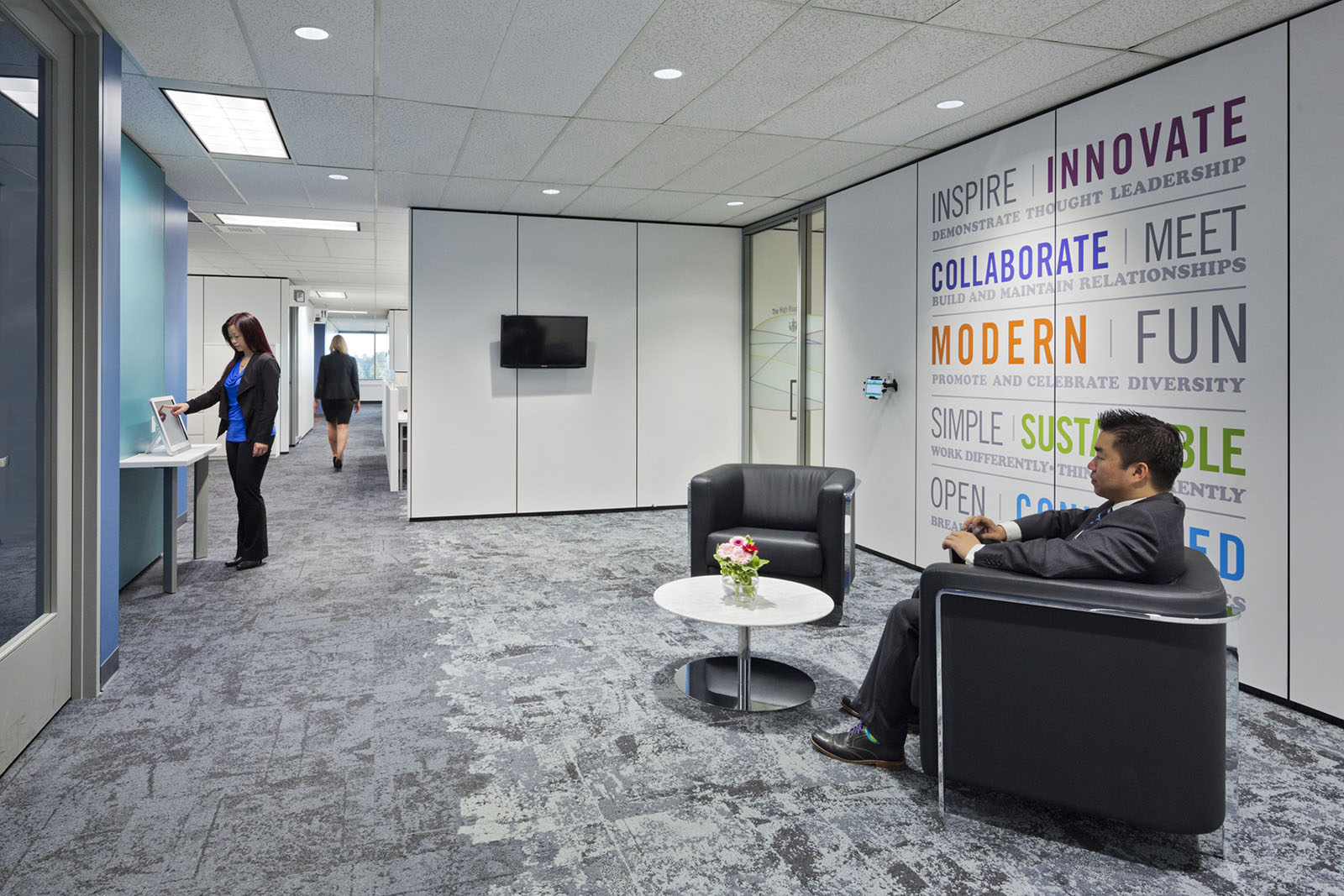 An office waiting area with a male businessman seated and two female figures.