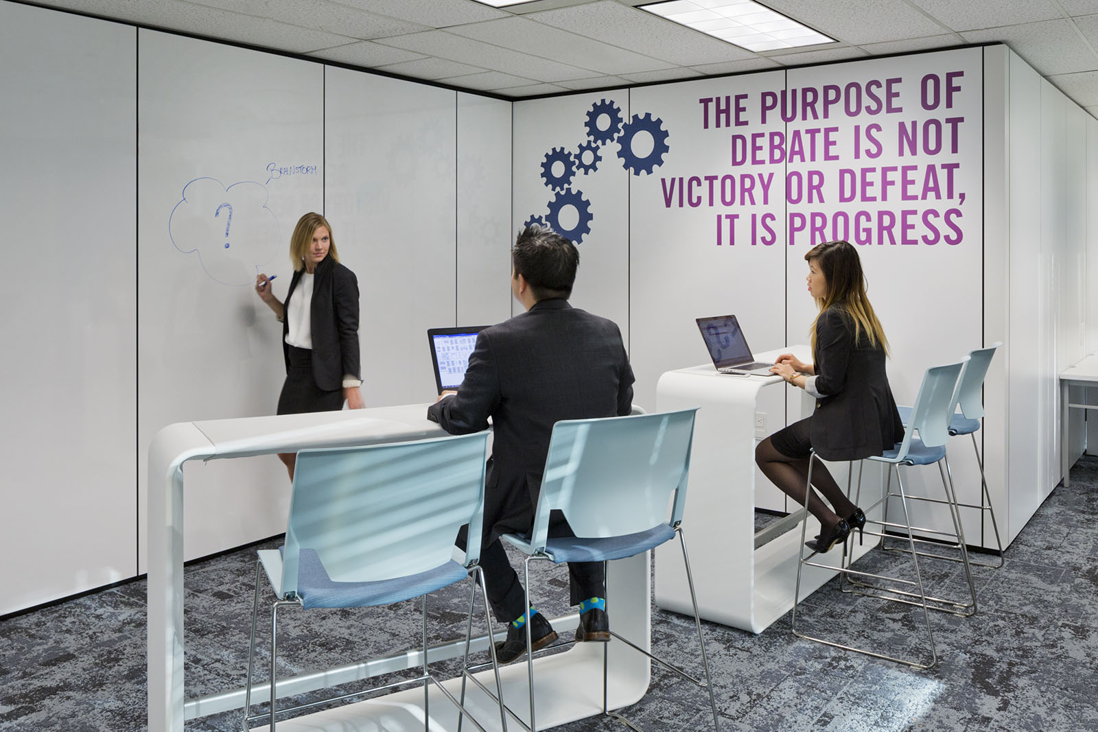 A female executive instructing two other executives.