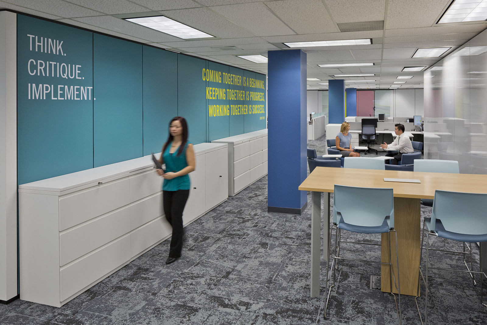 An office meeting area lined with filing cabinets, with a female figure walking towards camera