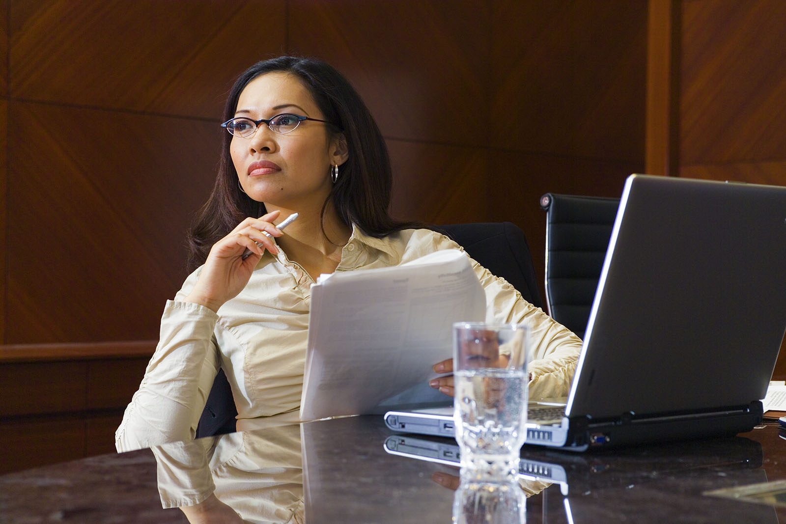 A businesswoman sitting in front of a laptop computer with pen and paper in hand.