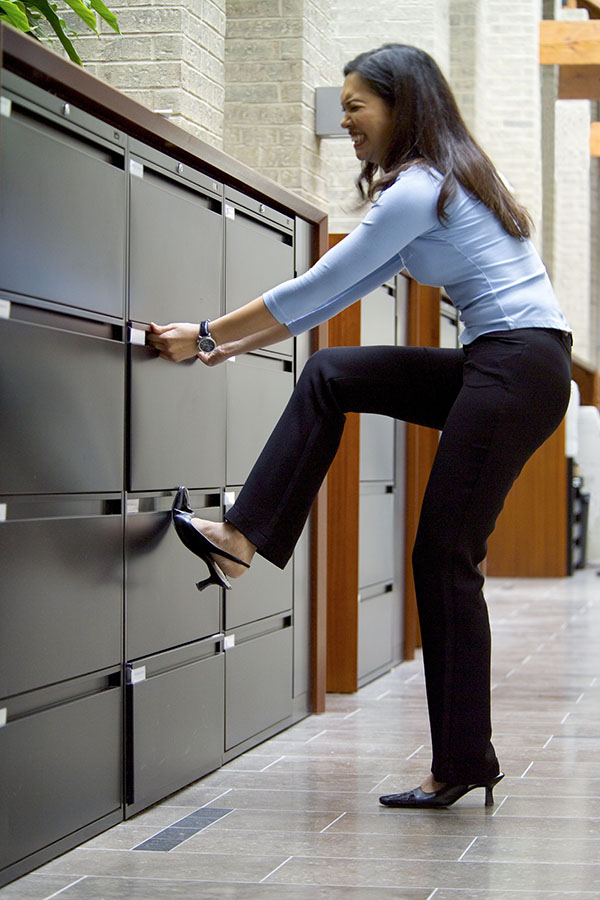 A woman trying to open a drawer to a filing cabinet.