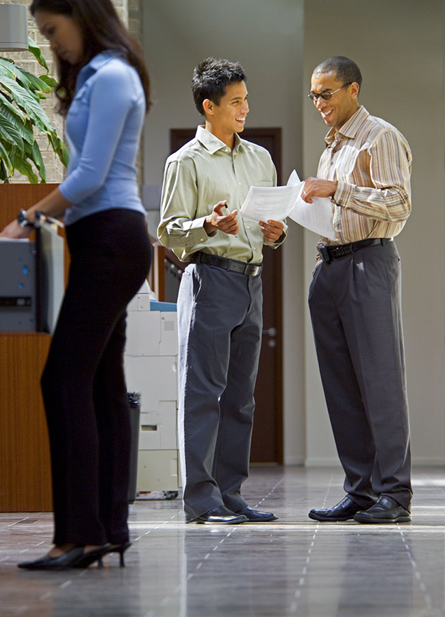Three office workers in an office common area.