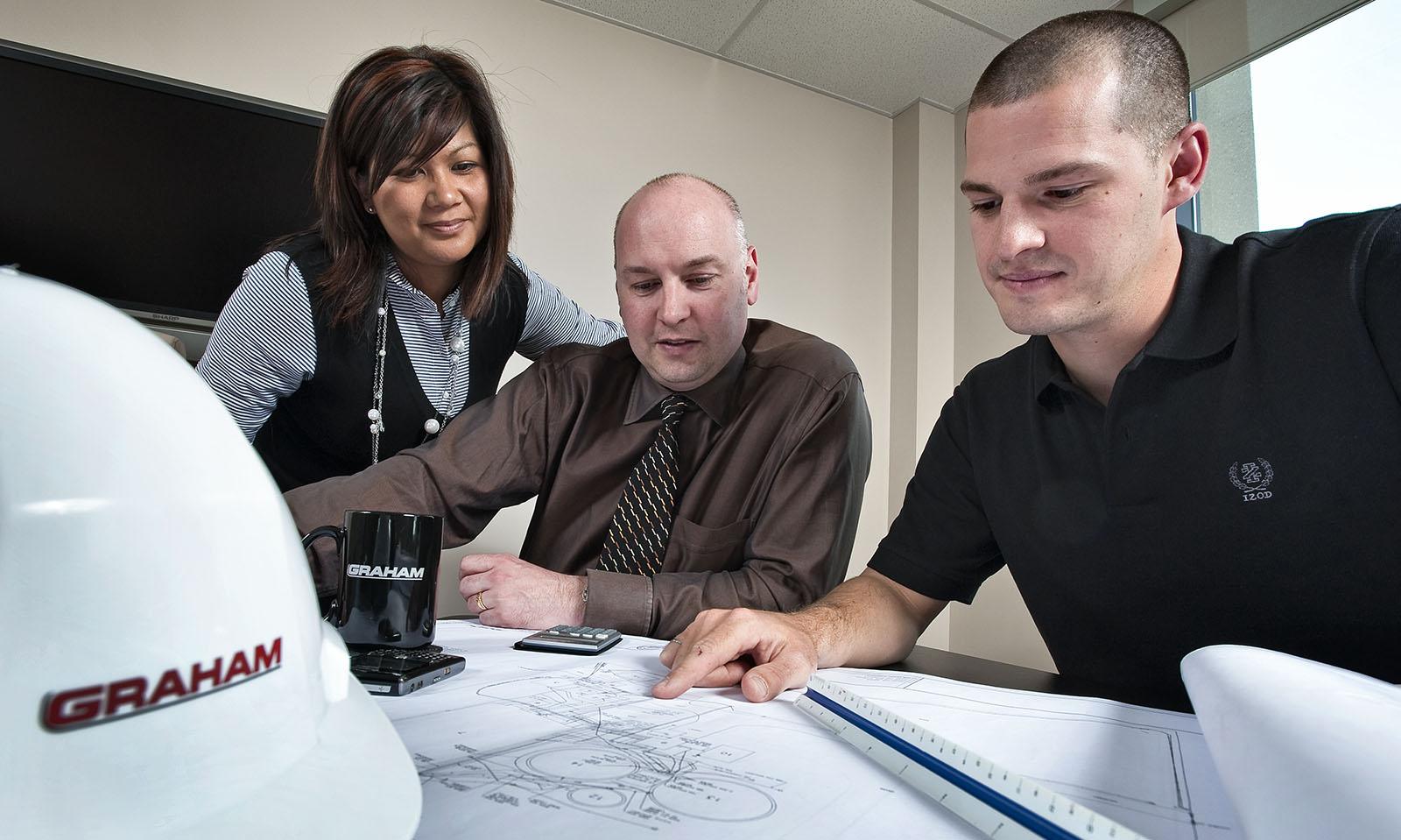 Three individuals viewing blueprints.