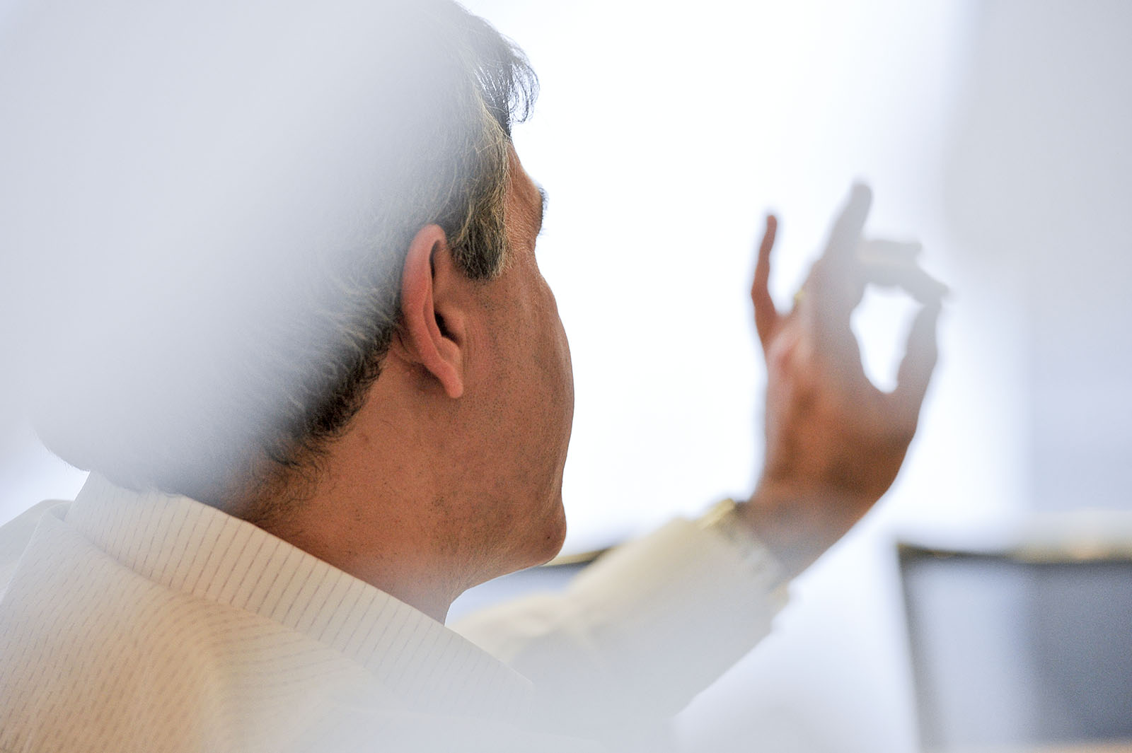 Over the shoulder view of a businessman making a gesture with his hand