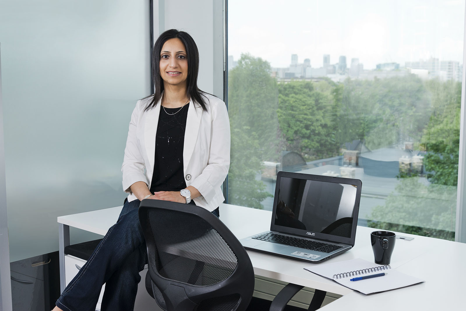 Female executive seated on office desk beside laptop
