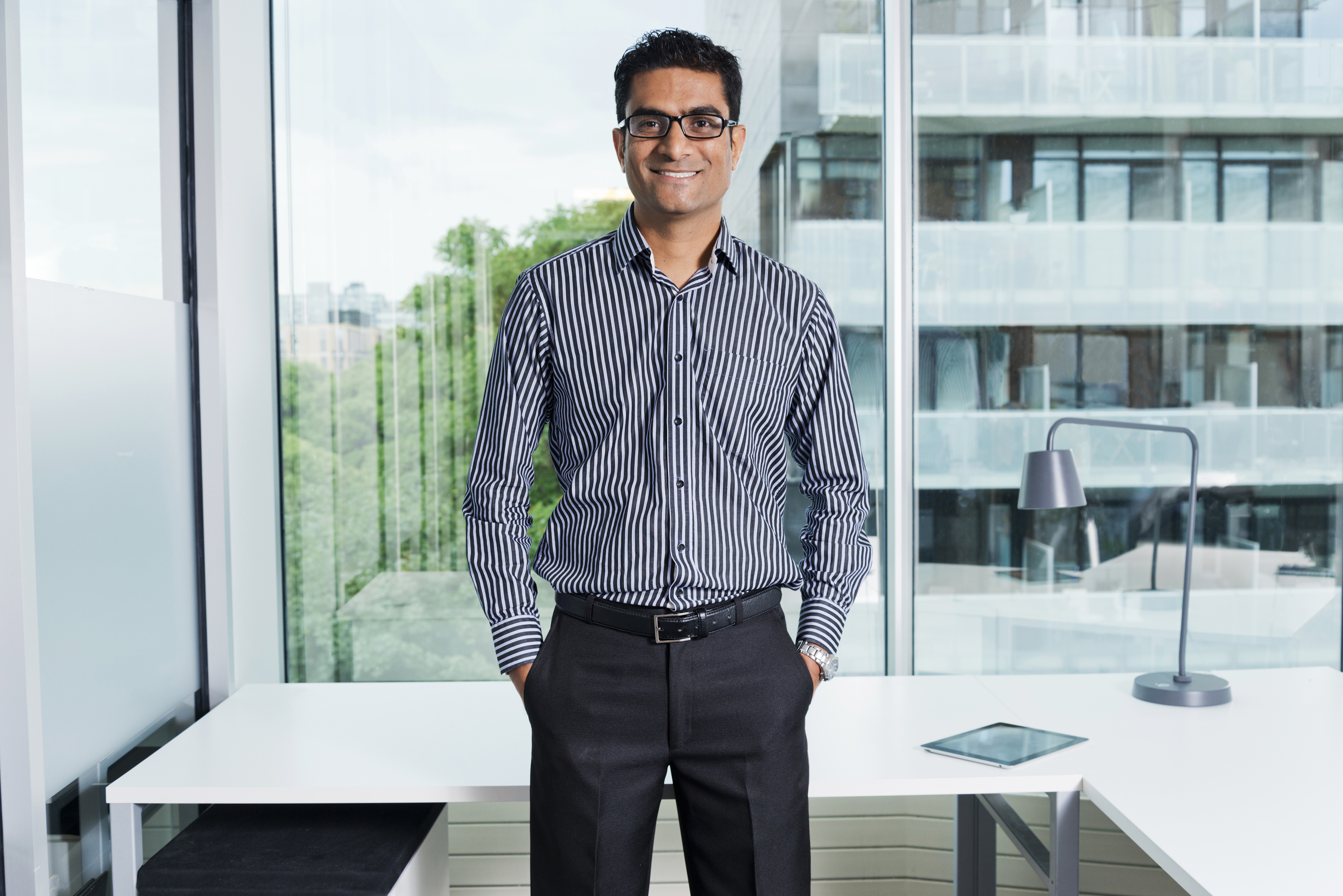 Male executive standing in office with hands in pockets