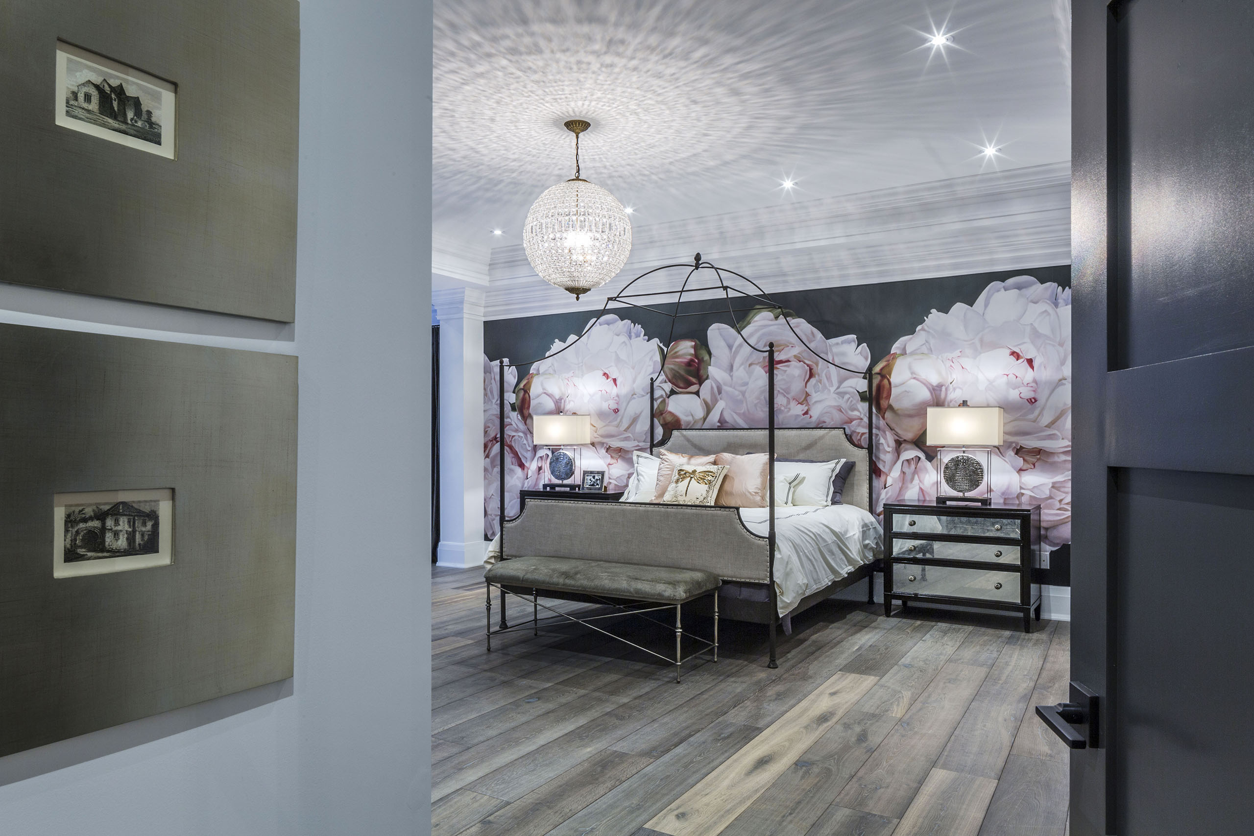 Bedroom with 4 poster bed, floral wallpaper and crystal light fitting.